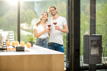 Young couple standing together with wine near the window of the modern apartment with green area outdoors celebrating housewarming