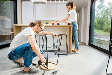 Young couple doing house chores assembling chair and doing order at the kitchen of the modern apartment