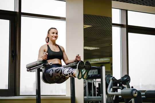 Portrait of sexy muscular girl wearing sportswear doing exercise on the bar raises his legs up, exercises on the press in the gym. Sport concept.