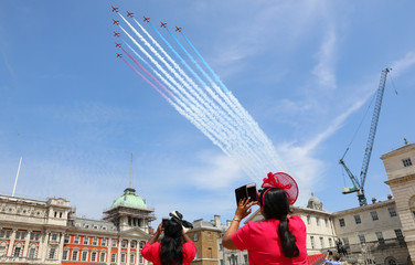 Members of the public photograph the Red Arrows display team as part of an RAF flypast for Trooping the Colour in central London