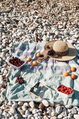 Summer composition with hat, berries and sunglasses on a pebbles beach near sea