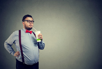 Man with overweight drinking sweet soda