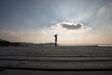 Side low angle view of a woman with arms outspread against cloudy sky