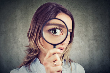 Curious woman looking through a magnifying glass Wall mural
