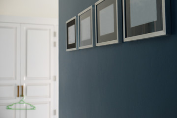 Blue color wall with four empty photo frames hanging and blurry background of cloth closet with one green coat hanger