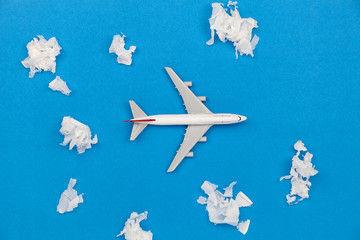 Airplane model with paper ball Instead of white clouds on blue background ,Preparation for Traveling and tour concept.