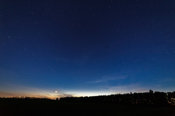 Bright star-planet Venus over the field and trees on the background of the starry sky at dusk.