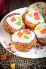Oat muffins with yogurt, candied fruit, red apple and cinnamon on dark wooden background.
