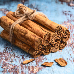 Bunch of fresh Indian cinnamon sticks on blue wooden table