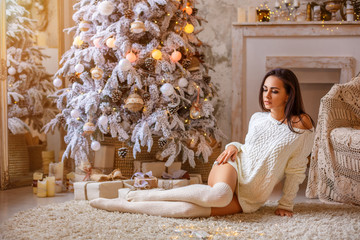 beautiful woman sitting near the Christmas tree on the floor in a white sweater and white leggings