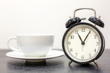 alarm clock on the table and white mug, tea time, rest concept