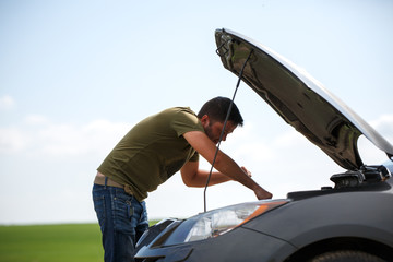 Image of young man mending broken car with open hood