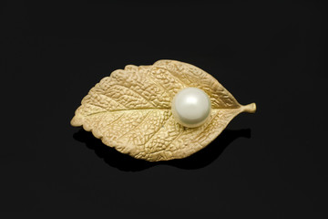 Wall Mural - golden brooch leaf with pearl isolated on black