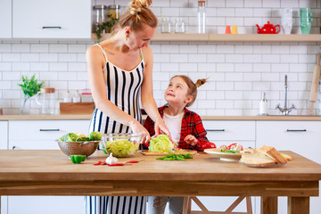 Photo of woman with daughter cooking food in kitchen
