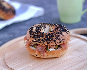 "Bagels ""New York"" with lightly salted salmon, cream cheese and dill, served on a wooden board"