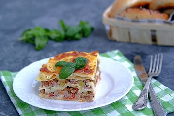 Lasagna with pork forcemeat, green peas and tomatoes on a dark gray concrete background.