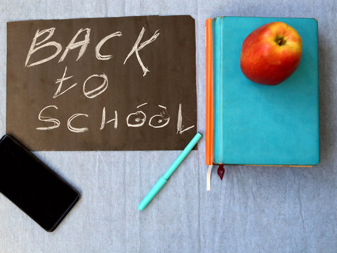 Blackboard with the Back to School text, yearbooks, mobile and apple, back to school concept