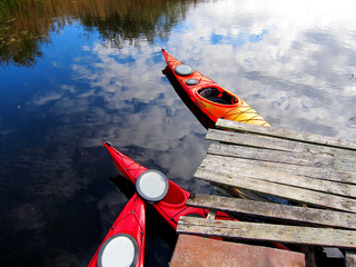 Three red kayaks under an old wooden bridge on the water with reflecting clouds
