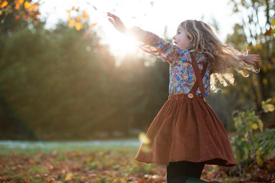Girl Dancing in a Green Field at Sunset in the Fall