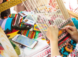 Hands of a girl weaving a Ukrainian mat made of multi-colored threads.