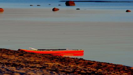 Deska windsurfing pozostawiona na brzegu morza po całodziennym pływaniu