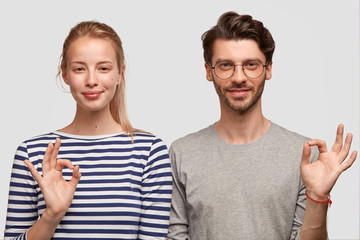 Shot of pleased happy woman and man show okay gesture, demonstrate their agreement, satisfied with good results of corporate work, isolated over white background. People and body language concept