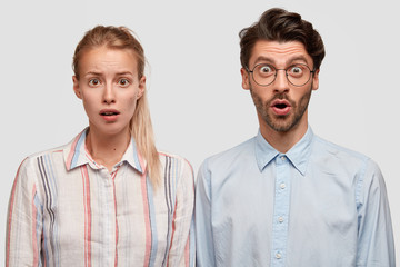 Portrait of stunned female and male colleagues have stupefied expressions, look with bated breath, being not ready to prepare deadline task, isolated over white background. People, cooperation concept