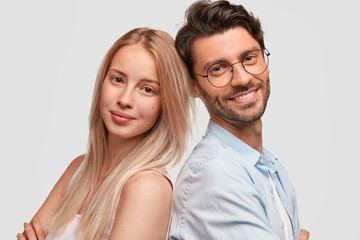 Close up portrait of lovely family couple stand back to back, pose for making shared photo, pose together against white background. Cute girl feels support of her husband. People and love concept