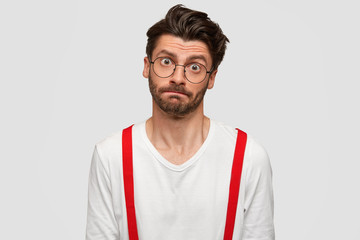 Handsome bearded young man looks with indifferent expression, has puzzled face, trendy hairstyle, hears something in bewilderment, isolated over white background. People and fashion concept.