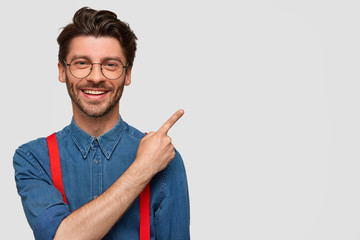 Cheerful pleasant looking young male with bristle, has good mood, smiles pleasantly, points with fore finger at blank space, advertises new products at shop, stands against white background.