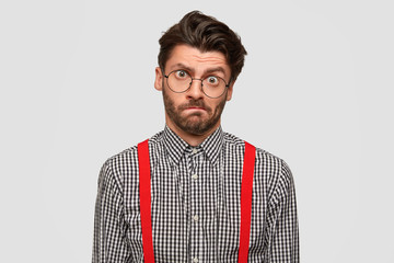 Displeased unshaven male frowns face, looks in puzzlement, wears checkered shirt with red braces, raises eyebrow, poses against white background. Unhappy young man has frustrated expression.