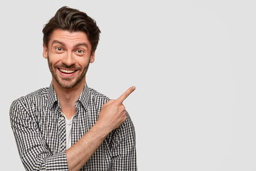 Fashionable male has cheerful expression, broad charming smile, wears checkered shirt, indicates with fore finger aside with blank copy space for your advertising content, invites you to sit there