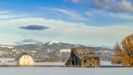 Old farmhouse with a wooden weathered barn in winter with mountains