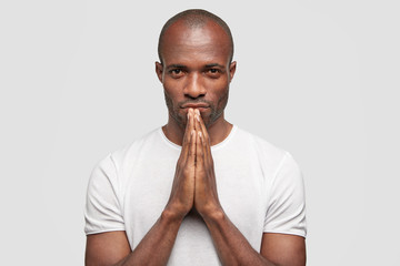 Candid shot of serious African American male has stubble, keeps hands in praying gesture, asks God for good fortune, believes in better life, isolated over white background. People and spirituality