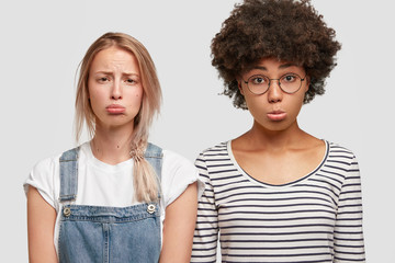 Beautiful abused women of different races, curve lips and have displeased expressions, express negative feeling, pose together against white background. African American female with best friend