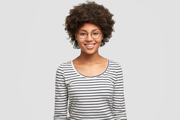 Positive emotions concept. Happy young smiling African American female in spectacles, rejoices unforgettable party with friend, dressed in casual striped jacket, isolated on white background