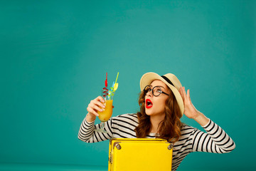 Portrait of young beautiful curl blond woman in hat with yellow big suitcase holding yellow cocktail over blue background