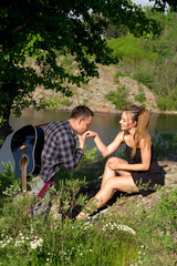 Young attractive man with guitar kissing hand of his beautiful girlfriend in park