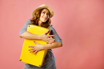 Young happy beautiful woman in hat holding yellow suitcase over pink background