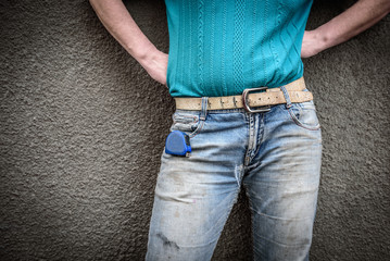 Construction old dirty and ripped jean. Worker with a construction measuring tape in a jeans pocket.