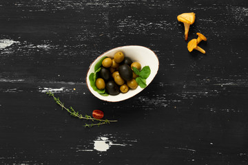 Black and green olives in bowl and bread slices topped with cream cheese lying on round plate standing on blue wooden surface with thyme and chanterelle mushrooms scattered around. Top view.