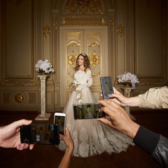 Guests take photographs of the bride on smartphones. Focus on smartphones.