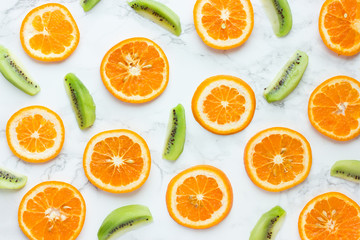 Healthy background orange and kiwi fruit slices on a white background top view