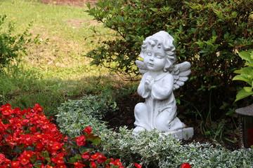 Grabengel zwischen Blumen auf dem Friedhof
