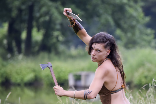 beautiful fighting celtic warrior woman with ax and sword in the field
