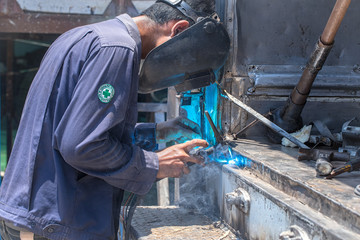 Welding in the industry by highly skilled technicians and wearing a safety mask.