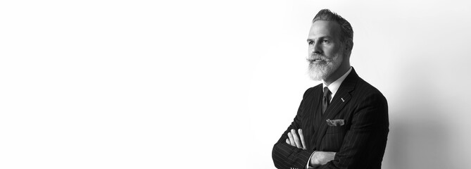 Portrait of bearded confident businessman wearing trendy suit over empty white background. Copy Paste text space. Wide. Black and White