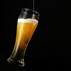 Pouring beer into glass over black background.