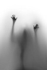 Help ! Spooky spirit, hands and fingers, and blurry body silhouette behind a textile curtain.