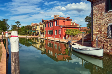 Torcello, Venice. Colorful houses on Torcello island, canal and boats. Summer, Italy